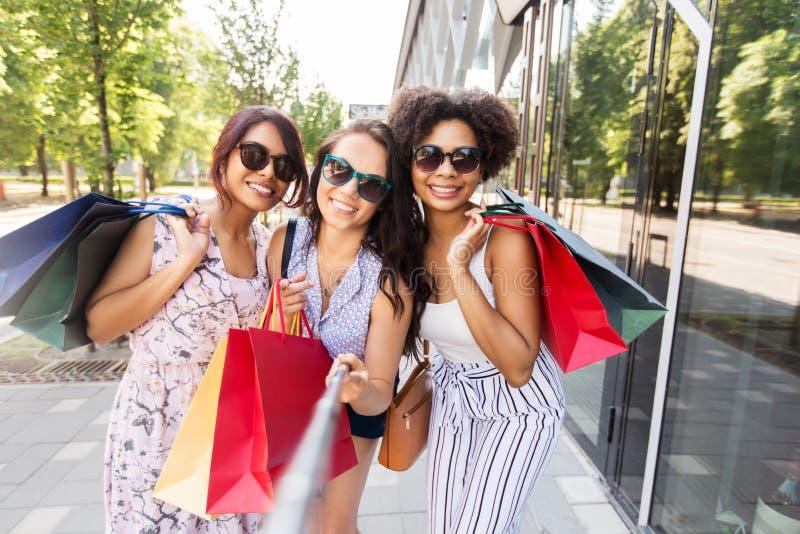 Kobiety z torba na zakupy bierze selfie outdoors obraz stock