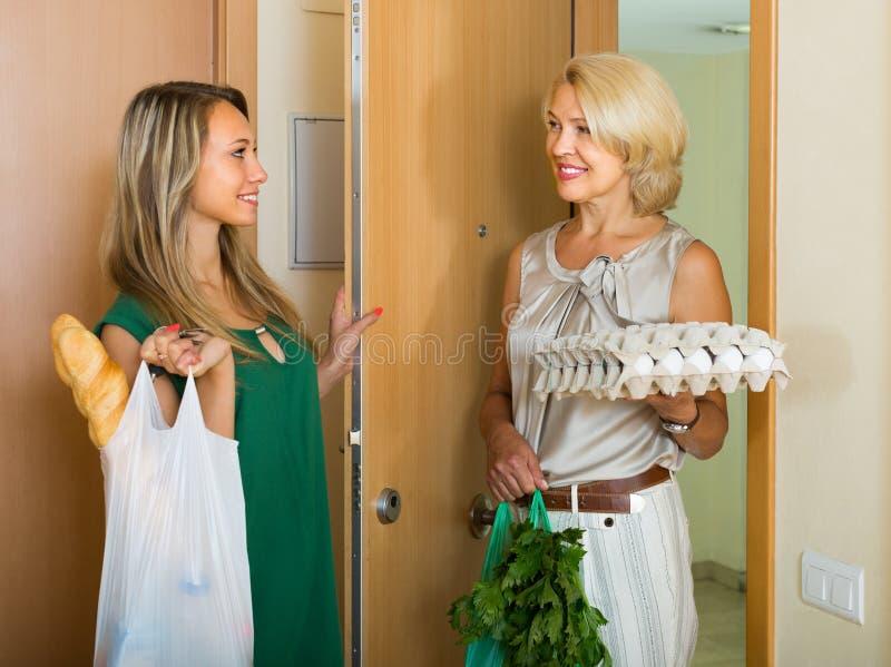 Kobiety z torbami karmowy pobliski drzwi fotografia stock
