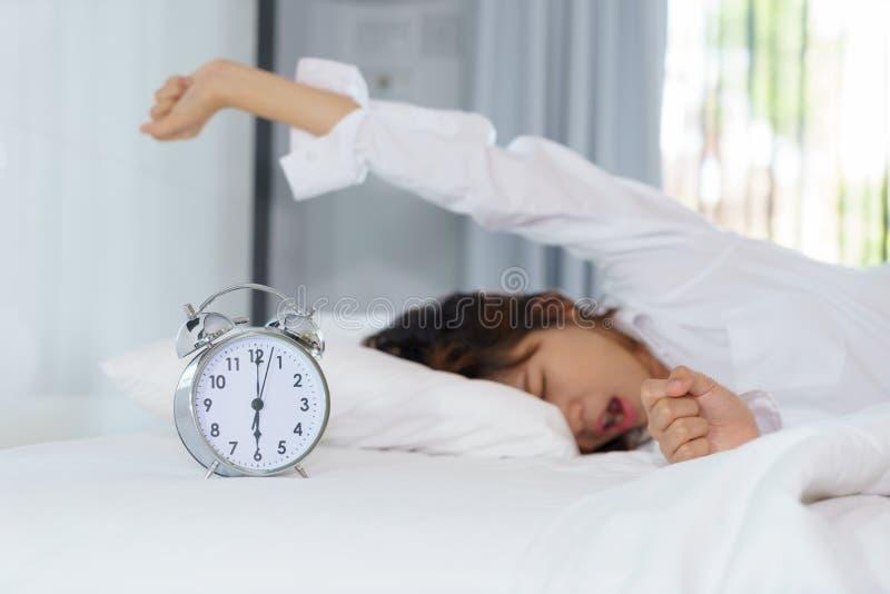 Kobiety ziewanie i rozciąganie podczas gdy budzący się up w ranku z zdjęcie stock