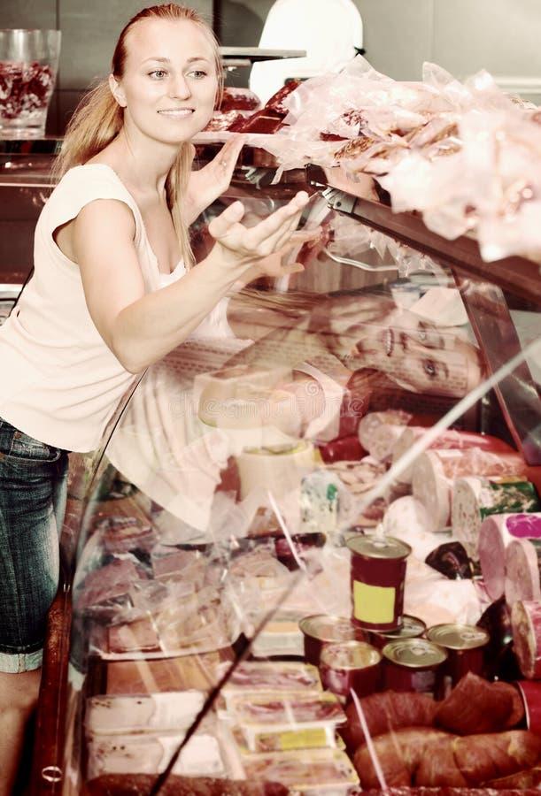 Kobiety zrywania salami kiełbasa w mięsnym sklepie zdjęcia stock
