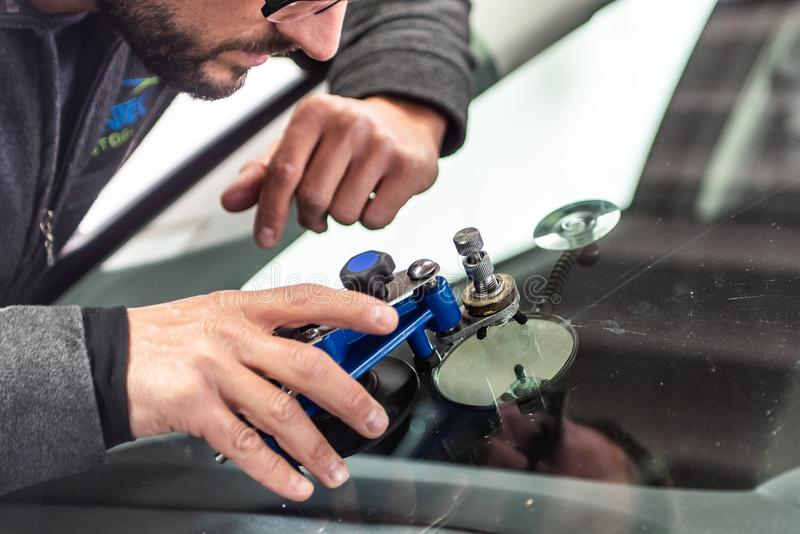 Koblenz Gerrmany 04.04.2018 man using repairing equipment to fix damaged cracked windshield at wintec company royalty free stock photography
