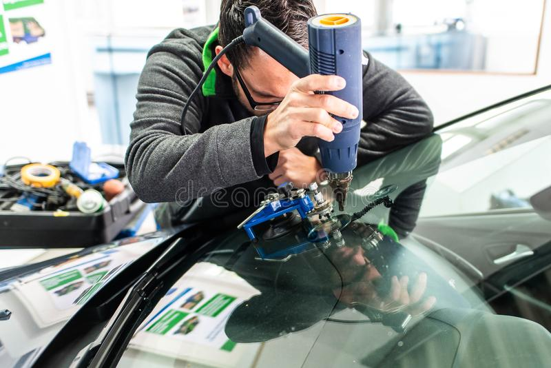 Koblenz Gerrmany 04.04.2018 man using repairing equipment to fix damaged cracked windshield at wintec company stock photo