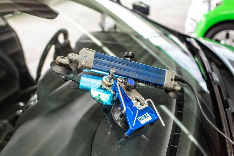 Koblenz Gerrmany 04.04.2018 man using repairing equipment to fix damaged cracked windshield at wintec company stock photography