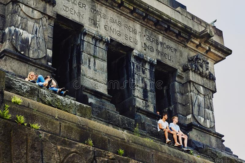 Koblenz, Rijnland-Pfalz, Duitsland, 10 Juni, 2018: De jongeren zit op een monument aan Wilhelm I op Deutsches Eck en tak stock foto's