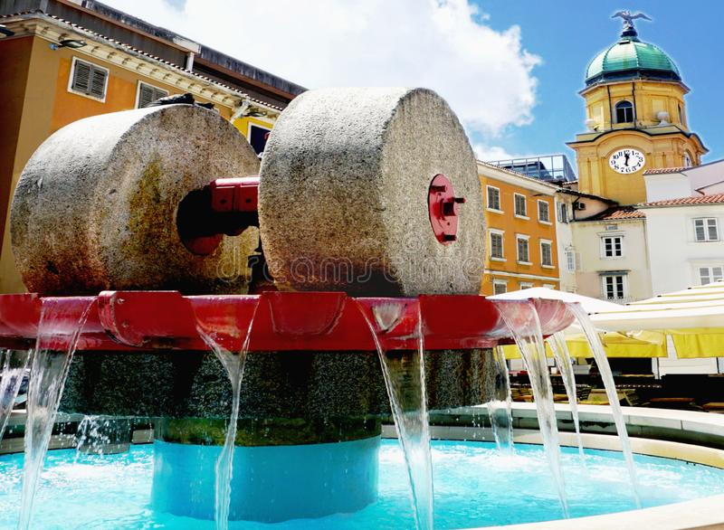 Kobler square in the Croatian town of Rijeka which is European capital of culture 2020. Big millstones in a fountain are a symbol. Of cultural heritage and stock photography