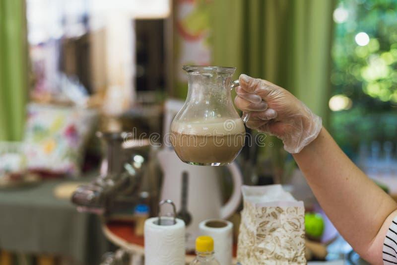 Koch gießt kochendes Wasser über der Hefe, um den Brei für den Teig zu erhalten Herstellung Teig durch die Verdünnung der Hefe mi stockbild