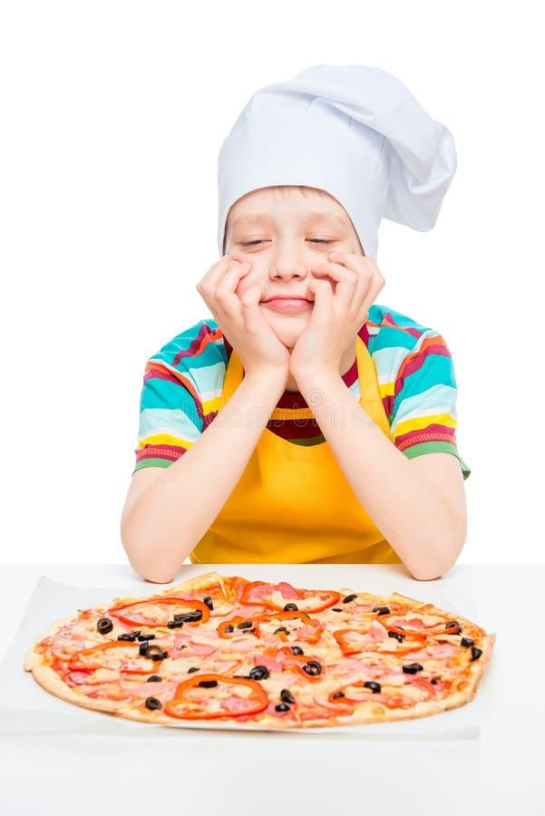 Koch mit selbst gemachter Pizza, Junge 10 Jahre alt, Porträt auf weißem Hintergrund stockbild