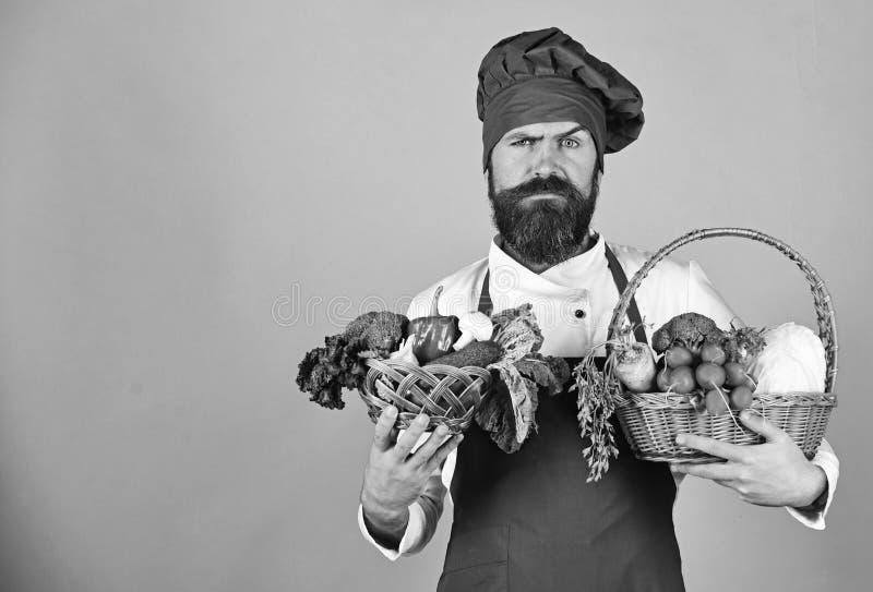 Koch mit strengem Gesicht in Burgunder-Uniform hält Gemüse lizenzfreies stockfoto