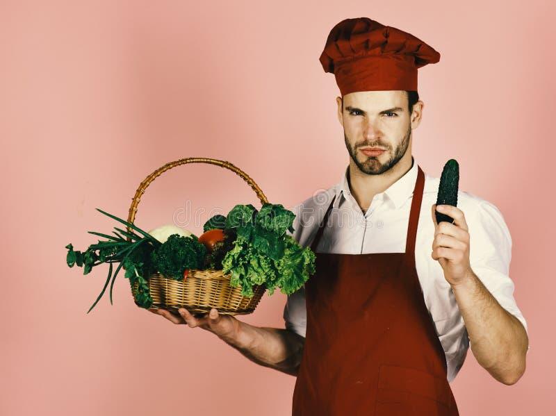 Koch mit strengem Gesicht hält Gurke und Weidenkorb von frischen Veggies Chef in Burgunder-Uniform hält Gurke stockfotografie