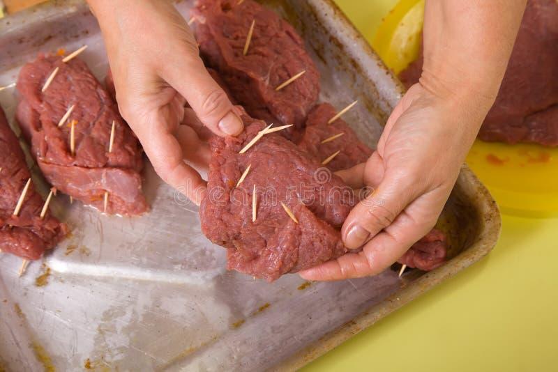 Koch setzt angefülltes Rindfleisch, um Bratpfanne zu kochen stockbilder