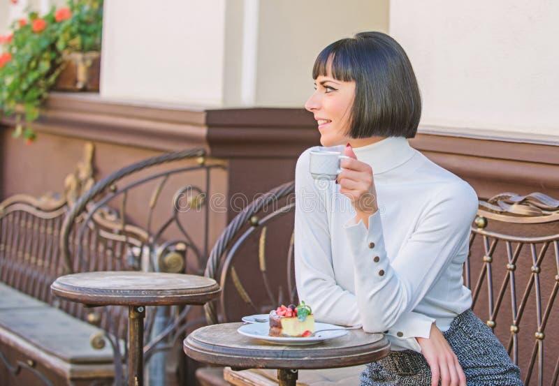 Kocha cukierki Kobiety atrakcyjna elegancka brunetka je smakosz kawiarni tarasu tortowego t?o Przyjemny czas i zdjęcia royalty free