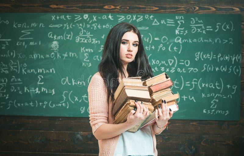 Kocha czytanie Dziewczyna głupek trzyma ciężkiego stos stare książki, chalkboard tło Dziewczyna móla książkowego wp8lywy książki  obrazy royalty free