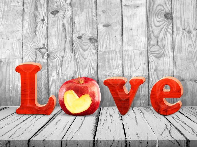 Kocha znaka z czerwonym jabłkiem na drewnianym stole fotografia royalty free