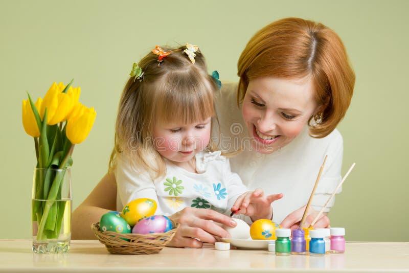 Kochająca mama i jej dzieciak maluje Wielkanocnych jajka zdjęcia stock