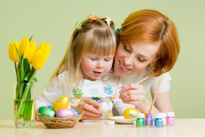 Kochająca matka i jej dziecko maluje Easter jajka obrazy royalty free
