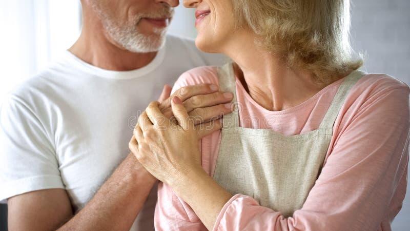 Kochająca starszego mężczyzny przytulenia żona w fartuchu, rodzinnym poparciu i opiece, szczęśliwy małżeństwo obraz stock