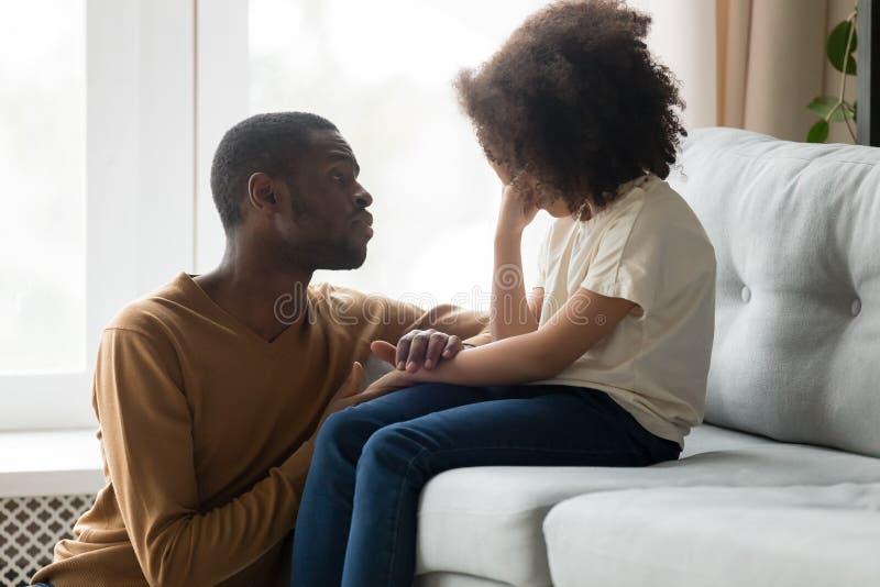 Kochający afrykański tata pociesza płaczu dzieciaka córki pokazuje empatię obrazy royalty free