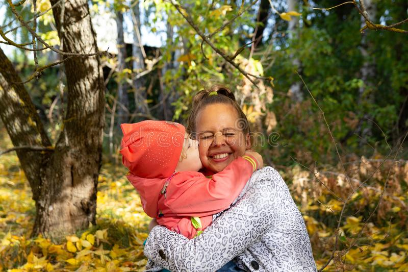 Kochający dziecko ściska mamy na policzku i całuje fotografia stock