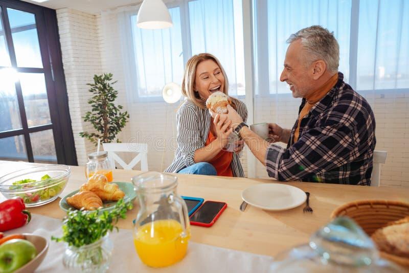Kochająca para dzieli dużego yummy croissant w ranku zdjęcia royalty free