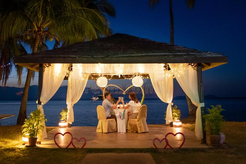 KochajÄ…ca para jedzÄ…ca romantycznÄ… kolacjÄ™ na tropikalnej plaży zdjęcie stock