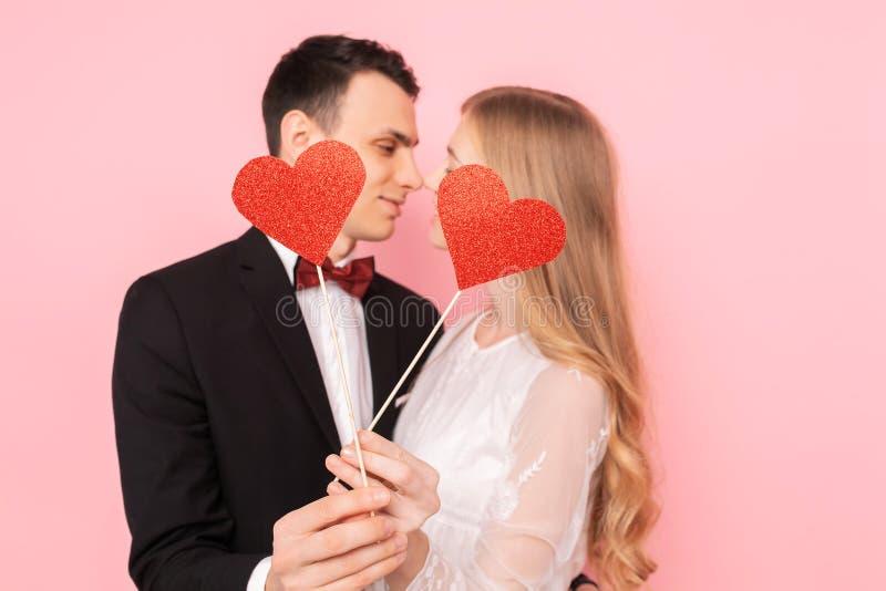 Kochająca para, mężczyzna i kobieta, trzymający czerwieni papierowych serca, ściska na różowym tle, kochanka dnia pojęcie zdjęcie stock