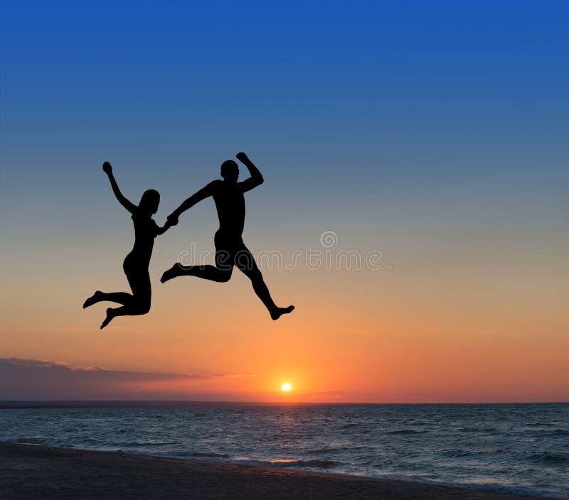 Kochająca para skacze wysoce w niebie przy miejscowością nadmorską zdjęcie stock