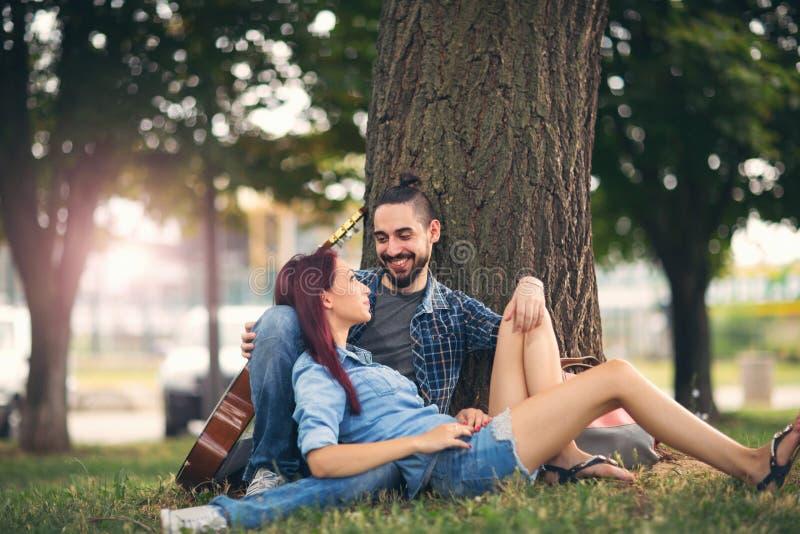 Kochająca para trzyma each innego obsiadanie na drzewnym bagażniku zdjęcie royalty free