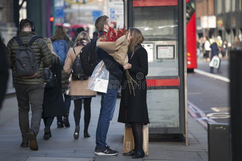 Kochająca para z czerwonymi shrubbery stojakami blisko telefonu budka fotografia royalty free