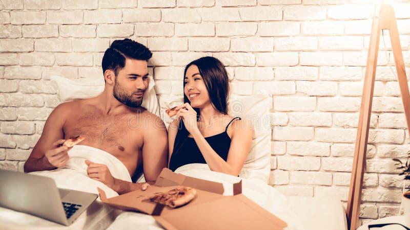 Kochająca pary dopatrywania filmu łasowania pizza w łóżku zdjęcia stock