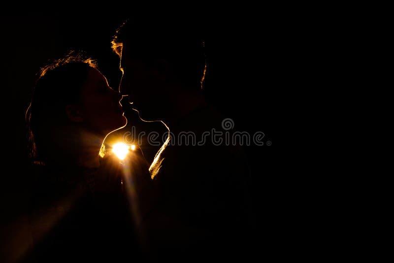 Kochająca pary pozycja w zmroku i jej sylwetka, zaświecamy promienie zdjęcie royalty free