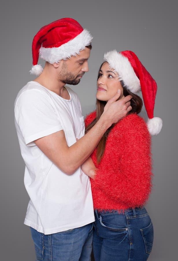 Kochająca potomstwo para w czerwonych Santa kapeluszach zdjęcie royalty free