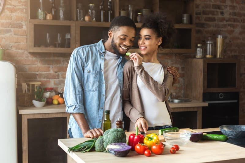 Kochającej afrykańskiej żony żywieniowy mąż podczas gdy gotujący obraz royalty free