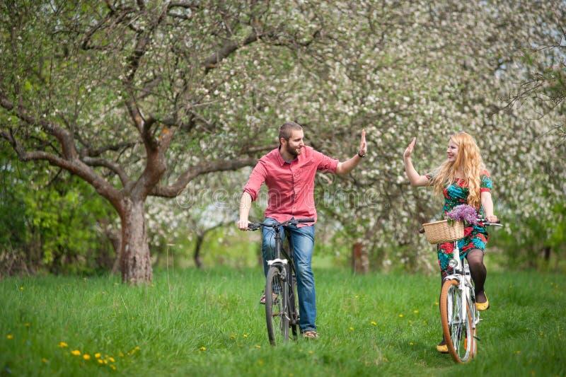 Kochającej potomstwo pary jeździeccy bicykle w wiośnie uprawiają ogródek obraz stock