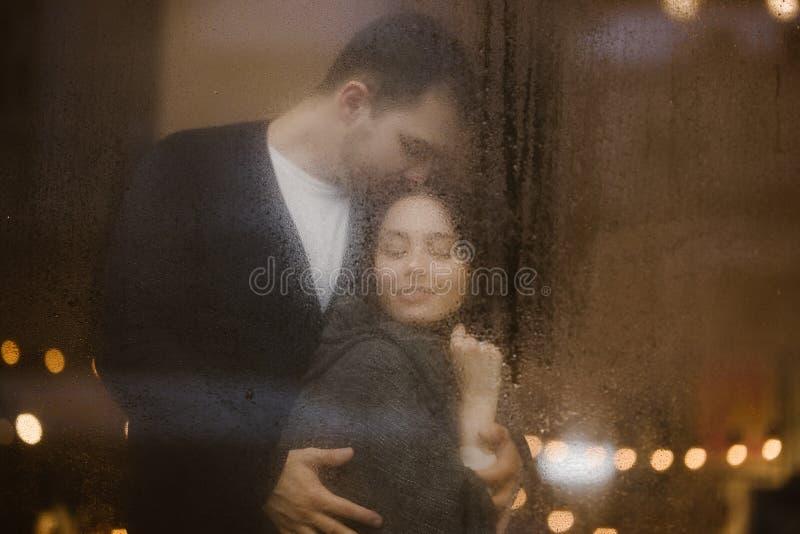 Kochający facet ściska jego dziewczyny pozycję za mokrym okno z światłami i całuje Romantyczna para fotografia stock
