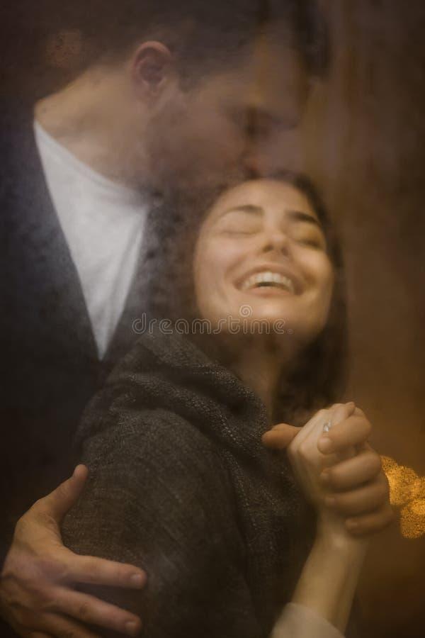 Kochający facet ściska jego szczęśliwą dziewczyny pozycję za mokrym okno z światłami i całuje Romantyczna para zdjęcia stock