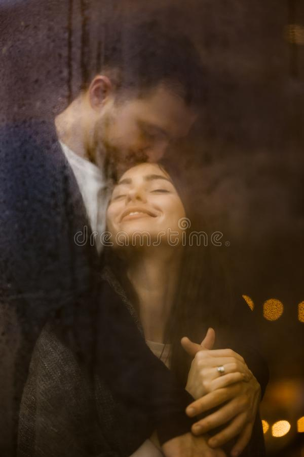 Kochający facet ściska jego szczęśliwą dziewczyny pozycję za mokrym okno z światłami i całuje Romantyczna para zdjęcie royalty free
