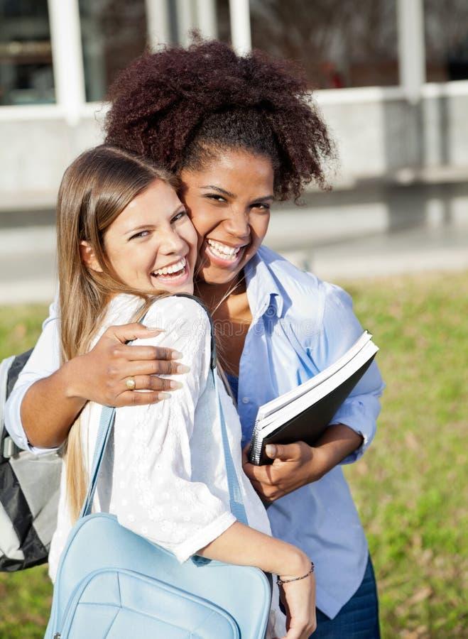 Kochający kobiety obejmowania przyjaciel Na szkoła wyższa kampusie obrazy stock