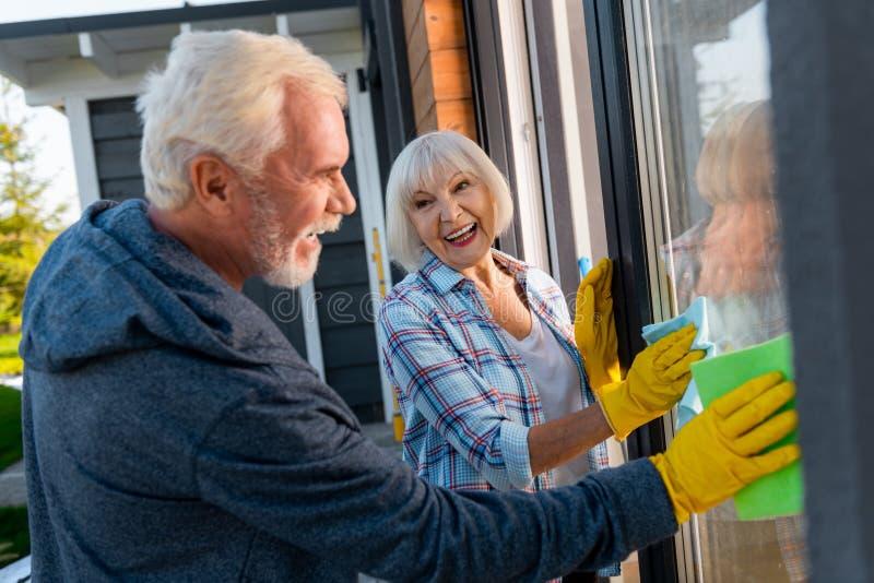 Kochający mąż pomaga jego ruchliwie żon płuczkowych okno outside domowi obrazy royalty free
