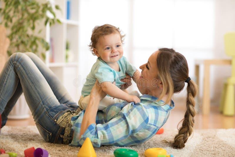 Kochający macierzysty łaskotanie jej małe dziecko na dywanie w domu fotografia stock
