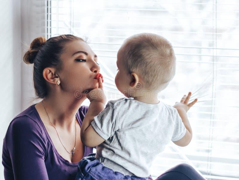 Kochający macierzysty bawić się z jej dziecka obsiadaniem na okno One czekanie coś obraz royalty free