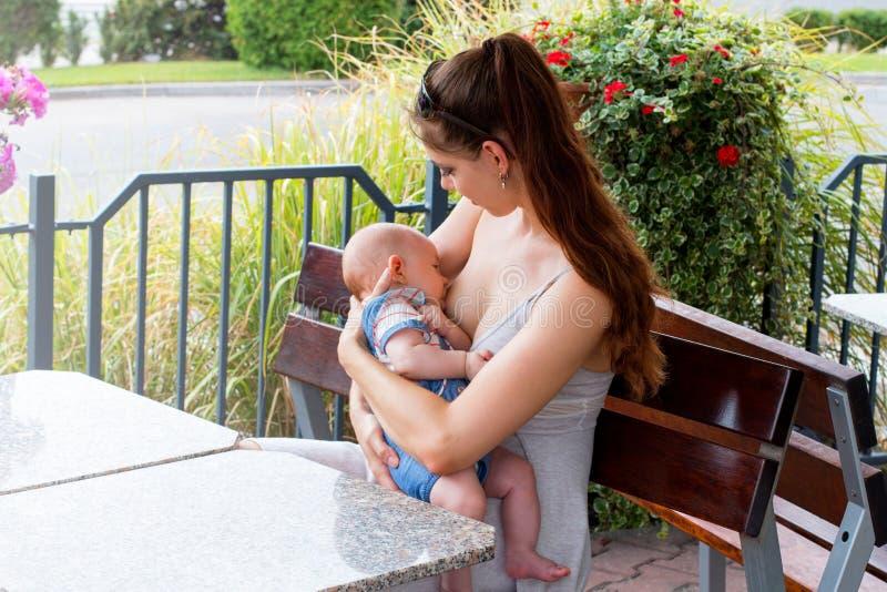 Kochający macierzysty karmiący dziecko, mamy mienia dziecko w rękach i breastfeeding outside podczas ładnego letniego dnia, siedz fotografia stock