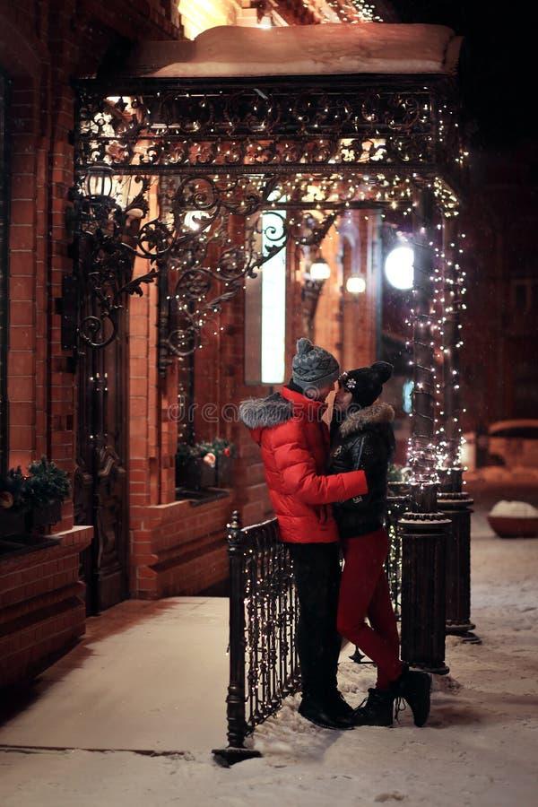 Kochający para uściski, stoi przy nocą blisko budynku dekorującego z girlandami St walentynki dzień, boże narodzenia obrazy stock