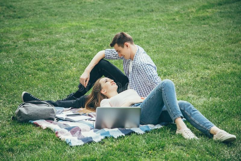 Kochający para ucznie relaksują po szkoły na gazonie zdjęcie royalty free