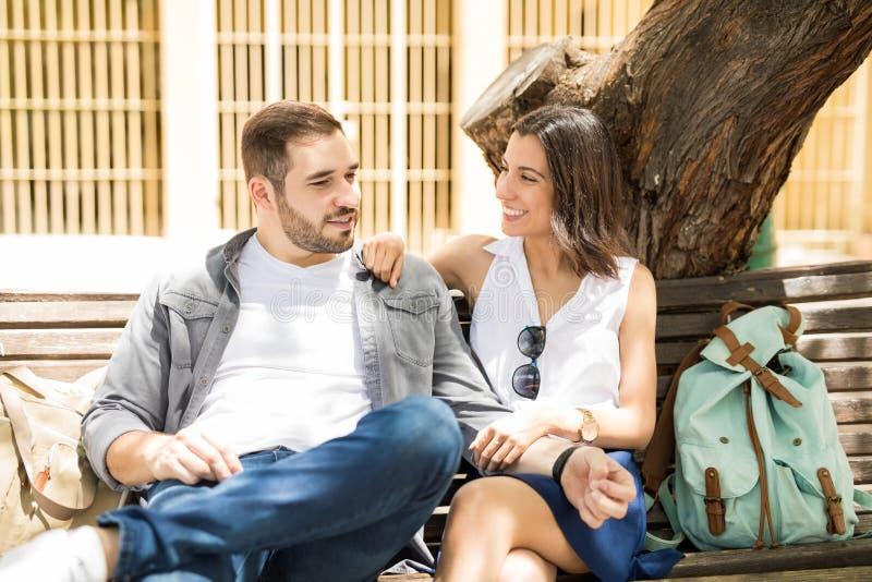 Kochający pary obsiadanie na ulicznej ławce przed drzewem obraz stock