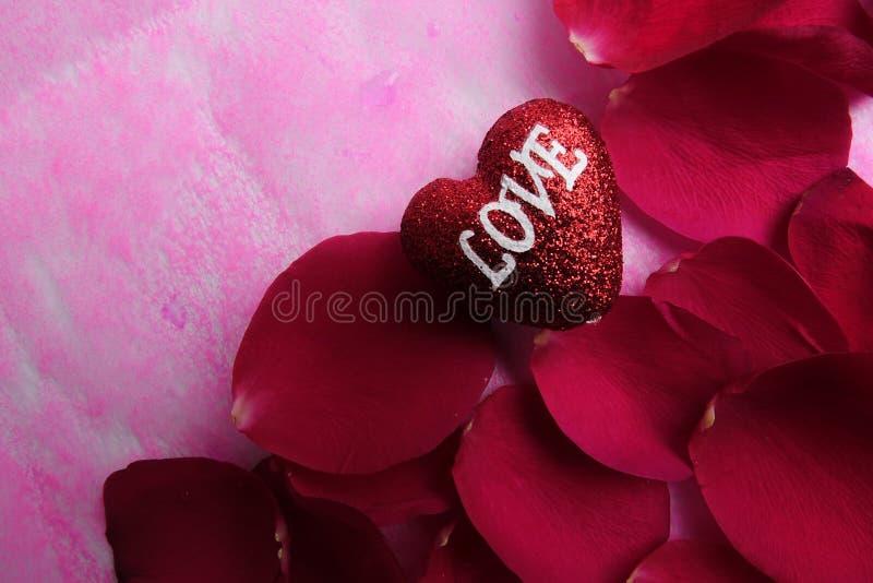 KOCHAJĄCY pojęcie z czerwieni róży płatkami i drukujący słowo miłość na czerwonym kierowym kształcie obraz royalty free