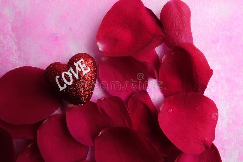 KOCHAJĄCY pojęcie z czerwieni róży płatkami i drukujący słowo miłość na czerwonym kierowym kształcie fotografia stock