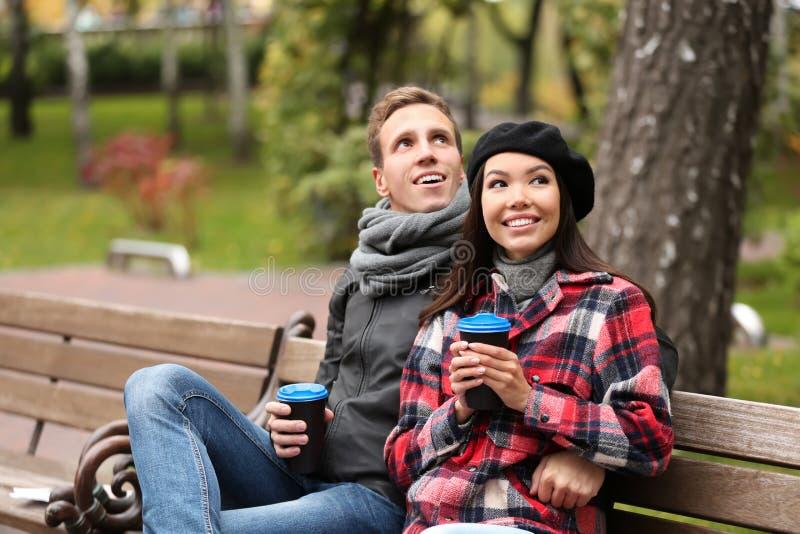 Kochający potomstwa dobierają się z kawowym obsiadaniem na drewnianej ławce w jesień parku obrazy stock