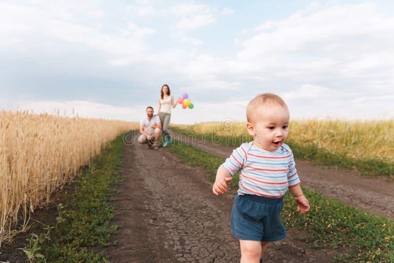 Kochający rodzice oglądają ich syna robić pierwszym krokom fotografia royalty free