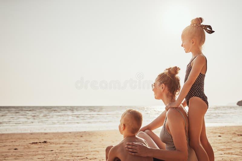 Kochający rodzinny obsiadanie na plaży patrzeje ocean fotografia stock