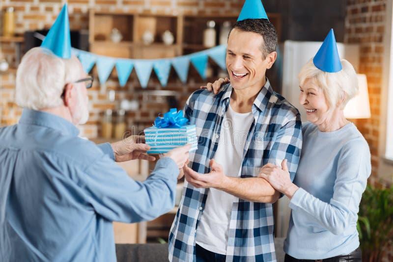 Kochający starszy ojciec gratuluje jego dorosłego syna z urodziny fotografia stock